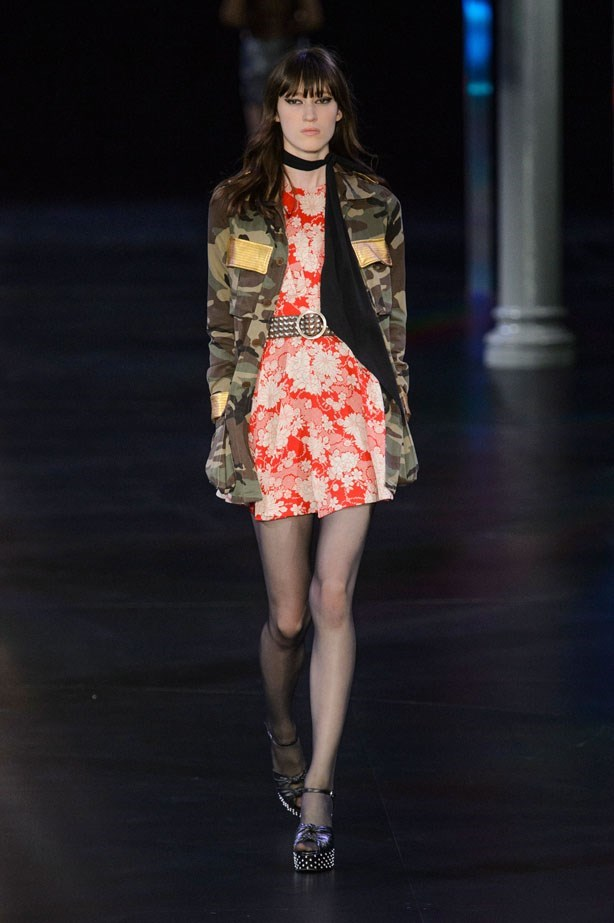 """<strong>Venue: Music Festival</strong> Doing the festival thing over new years, means light packing and easy-to-wear pieces, but of course, you still want to rock. Take some print-clashing cues from Saint Laurent and throw some camo (stolen from the boys, natch) over florals, find yourself a summer-of-love inspired cape as seen on Georgia May Jagger at Tommy Hilfiger, or copy-paste the 90s-esque halter dresses and boxy jackets at House of Holland. And don't forget your boots for stomping the mud. <br><br> <a href=""""http://www.elle.com.au/runway/ready-to-wear/ss15/2014/9/saint-laurent-ss15/"""">Saint Laurent SS15</a>"""