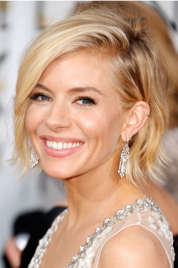 Sienna Miller wears fluttery lashes and a nude lip.