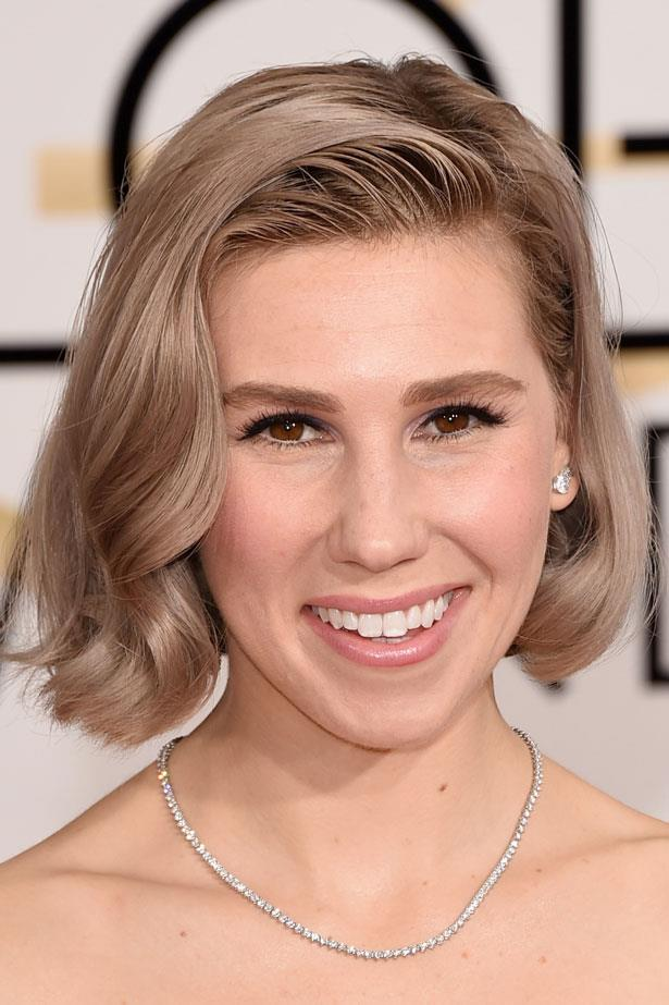 Zosia Mamet pulls off grey hair with bold brows and peach lip.