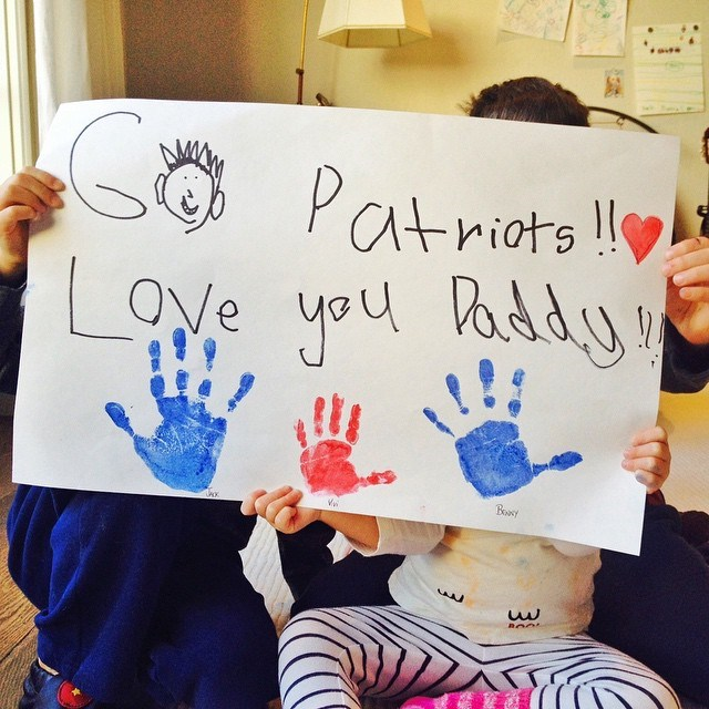 """Before kick off during the season, she shared two super cute photos on Instagram. The first a sign that read """"Go Patriots!! Love you Daddy!!!"""" signed with hand prints from the kids,  Jack, Benny, and Vivi. The """"O"""" in """"Go"""" appears to also be Tom Brady's head, which is pure genius."""