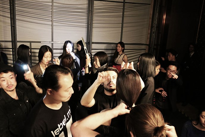 Frantic moments before the show with the final model line-up and hair and makeup teams touching up the models before the first girl is called.