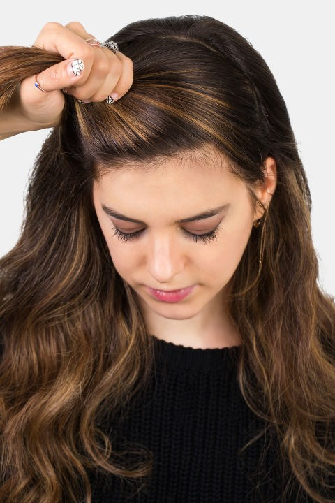 <strong>HALF-KNOT </strong> <br><strong>Step 1 </strong> <br>Begin by sectioning the hair as if you were wearing it half up. Gather the hair as if you were prepping for a ponytail (it's okay if it's not centred).