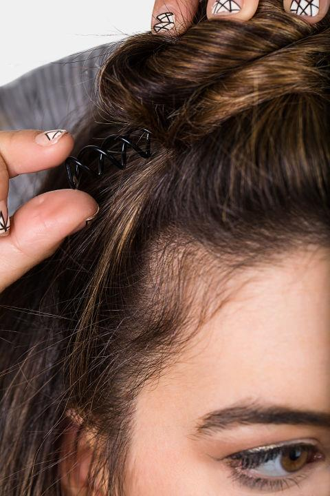 <strong>HALF-KNOT </strong> <br><strong>Step 4 </strong> <br>Secure by using a spiral pin or two. To finish the look, gently pull out a few pieces of hair around the ears and temples.