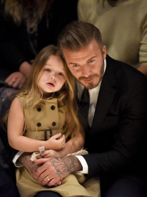 "Cuddling with dad David Beckham at the Burberry ""London in Los Angeles"" show."