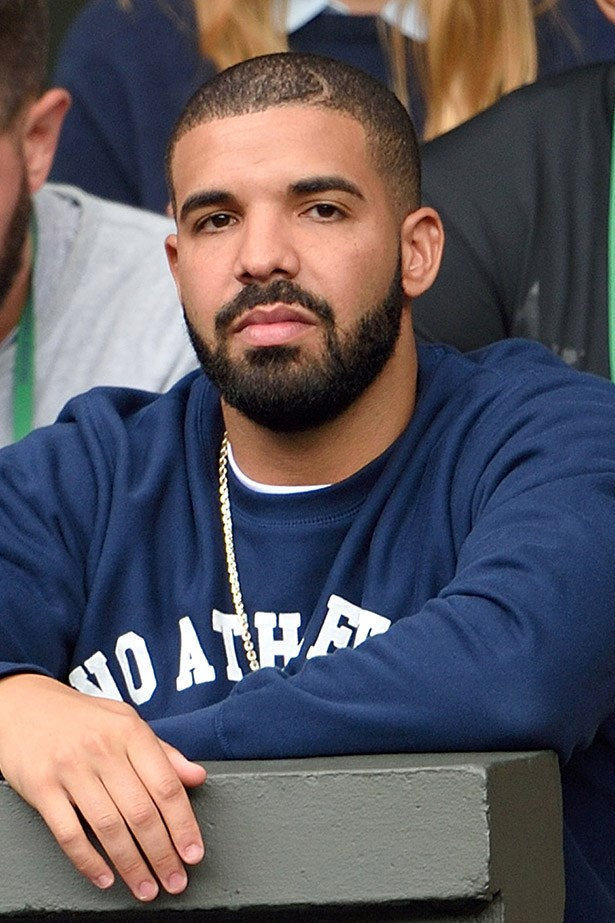 Drake, with a shirt on, watches on in a serious manner.