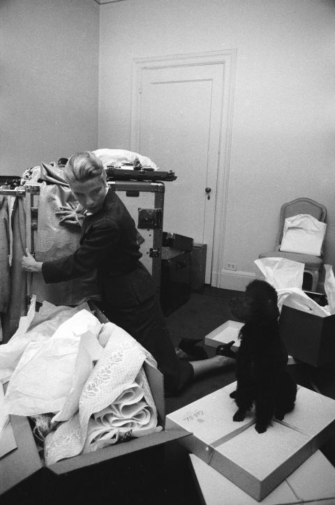 Glancing at her poodle, Oliver, while packing her clothes in March 1956.