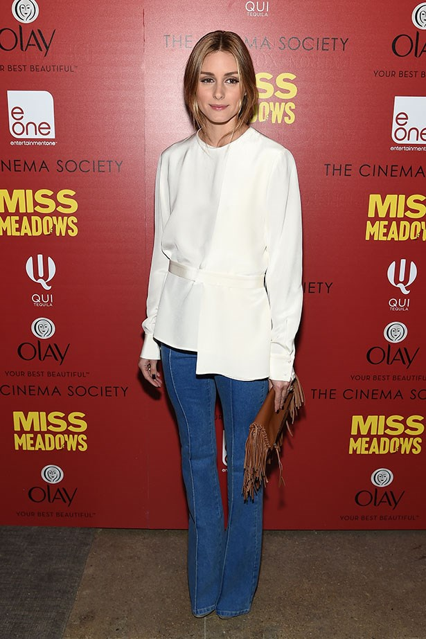 <p>Olivia Palermo styles her beloved Reiss flares with a fringed clutch.</p>