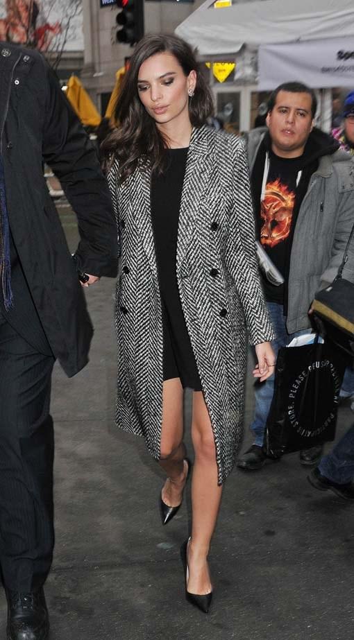 Emily dons a tweed coat.