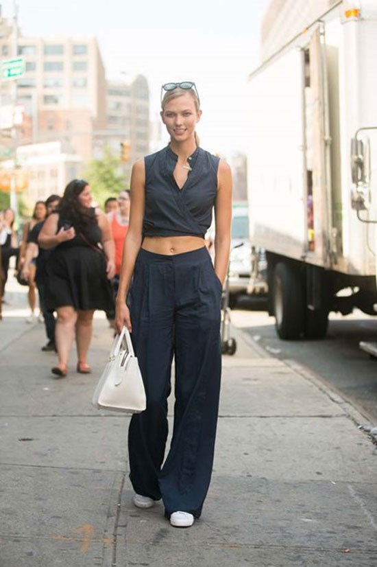 Karlie coordinates a laid-back crop top look with loose flare pants and sneakers.