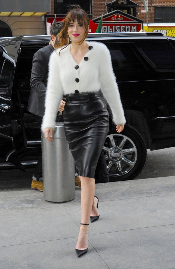 Dakota Johnson wearing a leather skirt and mohair cardigan in midtown manhattian.