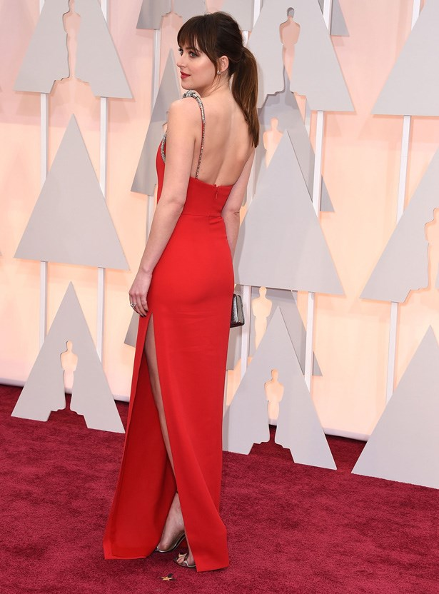 Dakota Johnson makes a bold statement in red as she arrives at the 2015 87th Annual Academy Awards.