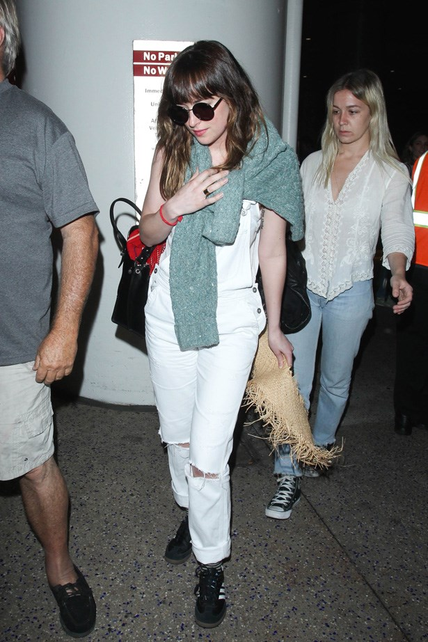 Leaving LAX in white denim overalls.