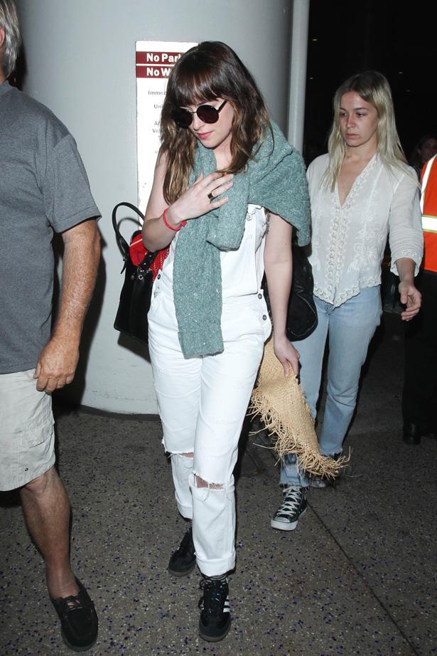 Leaving LAX in white denim overalls.