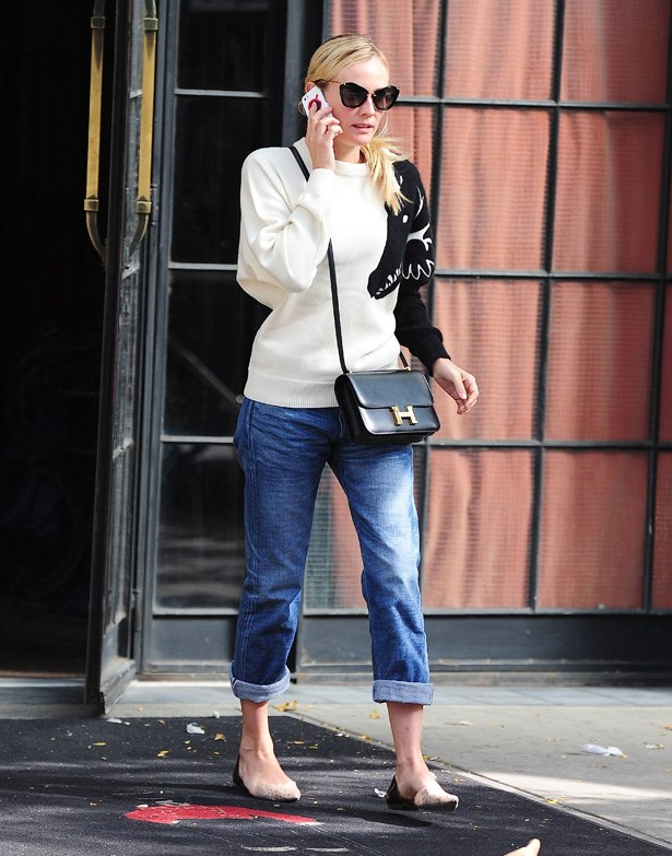 Kruger styles boyfriend jeans with Miu Miu sunglasses and an Hermes cross body bag.