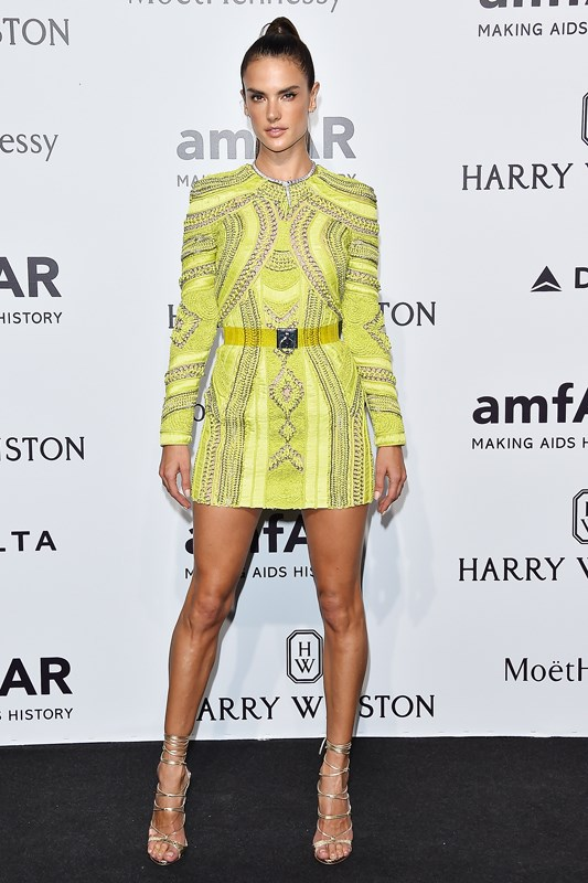 Alessandra Ambrosio showcases her killer legs in a thigh-skimming minidress by Balmain at the amfAR gala in Milan