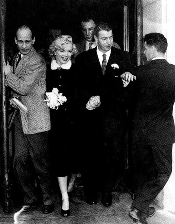 Marilyn Monroe wore a tailored black dress with a fitted coat (complete with white fur collar) and, of course, white silk gloves.