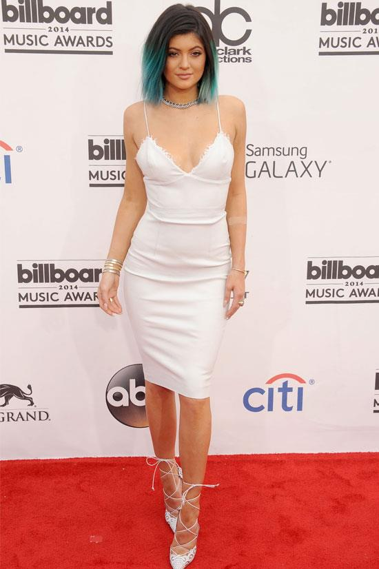 Kylie strikes a pose in this white dress and white strappy heels.