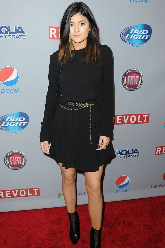 A younger Kylie rocks this simple black dress with a gold chain belt.