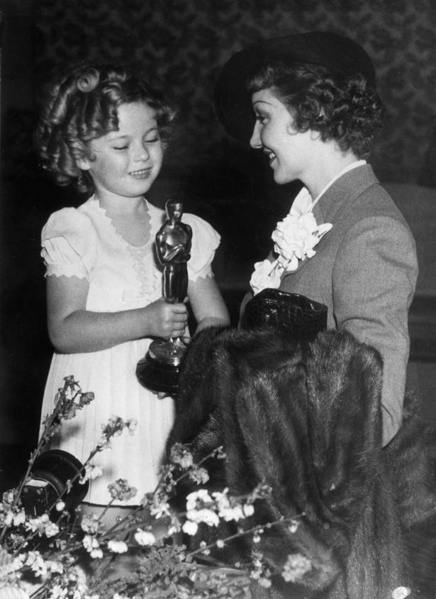 It's hard to look cute next to Shirley Temple but Claudette Colbert manages in her grey suit with flower appliques in 1934.