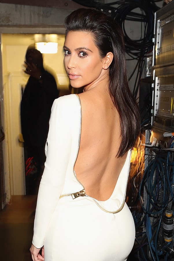 Kim Kardashian looking over her shoulder in a white dress