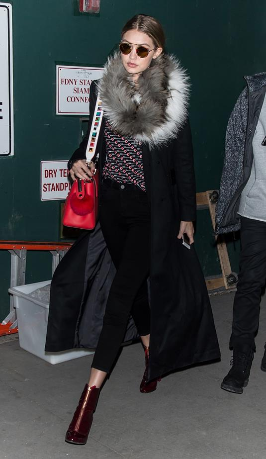 Whilst in New York for fashion week, Gigi was spotted wearing black trousers, boots, a duster coat and a fur scarf.