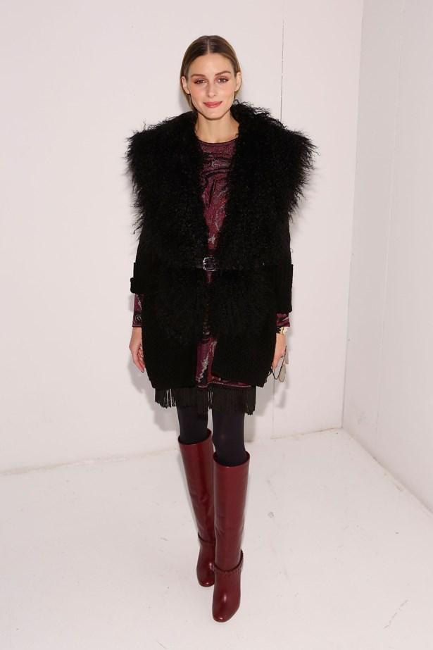 Olivia threw a fluffy black jacket on top of her red patterned dress and knee-high red boots.