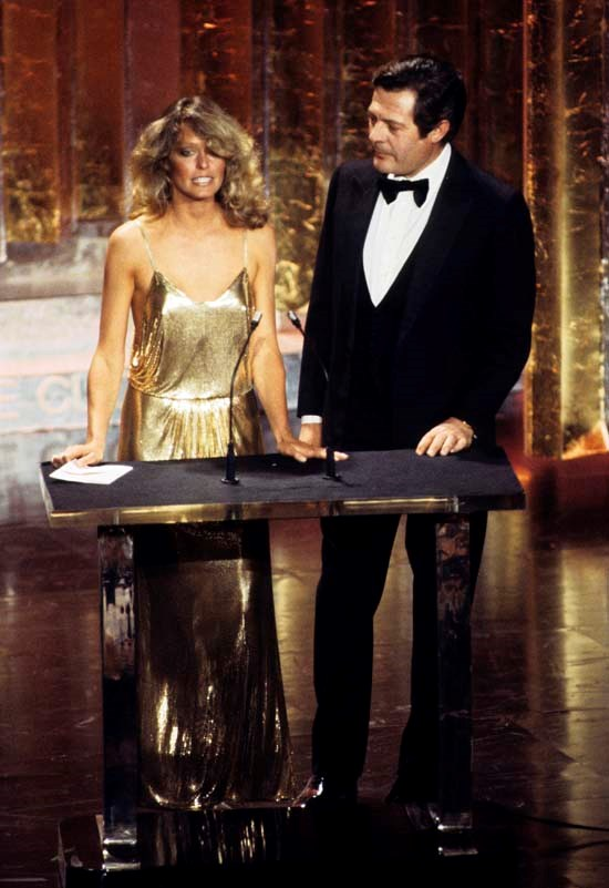 <strong>Farrah Fawcett</strong>, 1978 <br><br> <strong>Designer:</strong> Stephen Burrows <br> <strong>Why we love it:</strong> This golden slip dress was so ahead of its time. Farrah Fawcett looked absolutely magical in it, and it was definitely talk of the town.