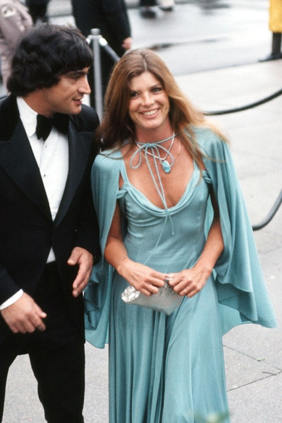<strong>Katharine Ross</strong>, 1975 <br><br> Designer: Unknown <br> <strong>Why we love it:</strong> The tie-around cape is a very modern touch to this gown. The whole design is simple but impactful.