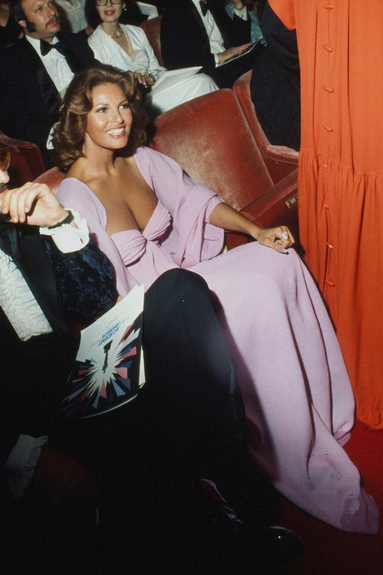 <strong>Raquel Welch</strong>, 1975 <br><br> <strong>Designer:</strong> Unknown <br> <strong>Why we love it:</strong> Another absolute winner from Welch, this gown is beautifully feminine. The shawl is a super elegant touch.