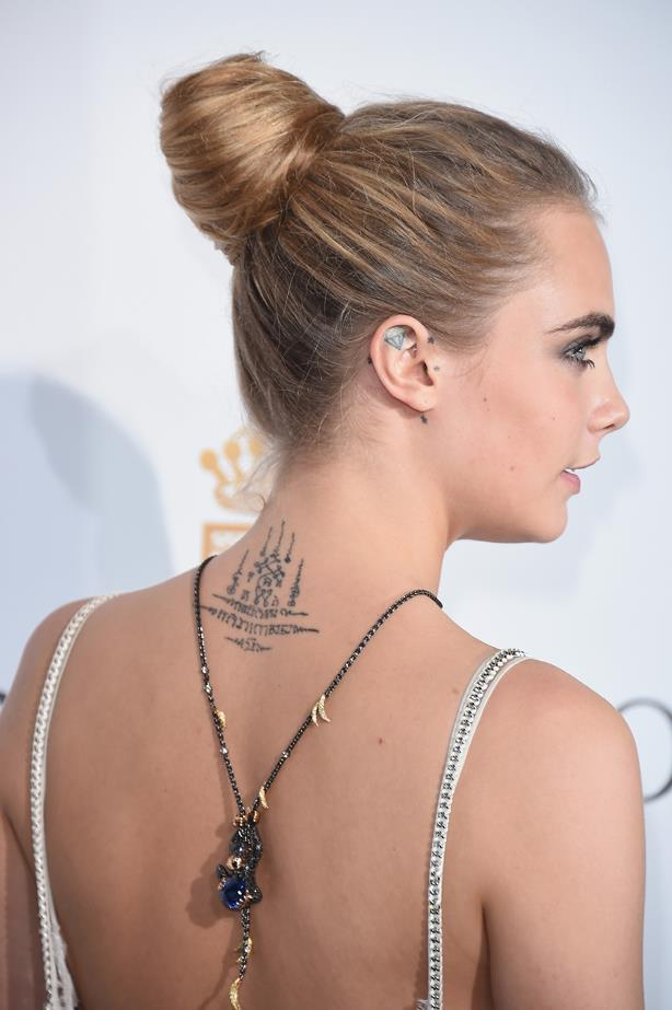 In addition to this piece on the back of her neck, Cara also has a lion tatooed on her index finger, 'Made In England' on the bottom of her foot and her initials on the side of her hand.