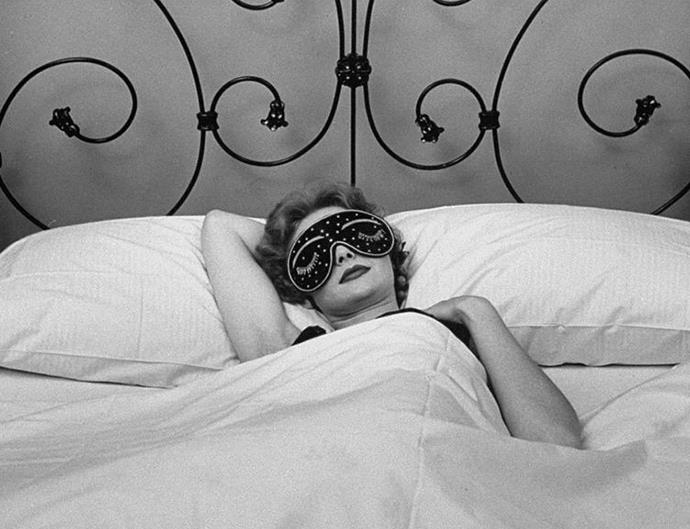 Woman in bed in sleeping mask.