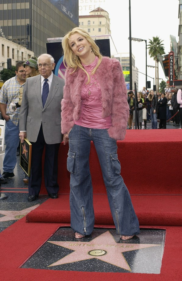Flared blue jeans with zipper details, a fluffy pink jacket and a ruched top? It must be 2003.