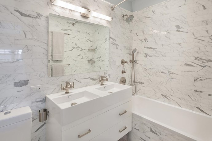 The bathroom boasts Carrera marble, a giant tub, his-and-hers sinks, and heated floors.