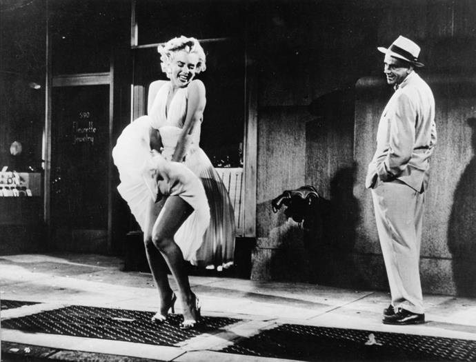 """<p><strong>MARILYN MONROE, 1955</strong><p><p> Marilyn Monroe wore her most famous white halter dress (with two pairs of underwear for safety) in the film <em>The Seven Year Itch</em>. """"Ooh, do you feel the breeze from the subway? Isn't it delicious?"""" she asks <a href=""""https://www.youtube.com/watch?v=ej5vaUwDsp8"""">in the scene</a> as the pleated skirt of her dress by costume designer William Travilla blows up. The scene was first shot on location in New York City, but thousands of onlookers were making so much noise that it had to be reshot on a set. Monroe's then-husband Joe DiMaggio was on set during filming and was reportedly <a href=""""http://www.theguardian.com/film/filmblog/2014/sep/15/marilyn-monroe-seven-year-itch-dress"""">so upset</a> by it that it caused the breakdown of the marriage."""