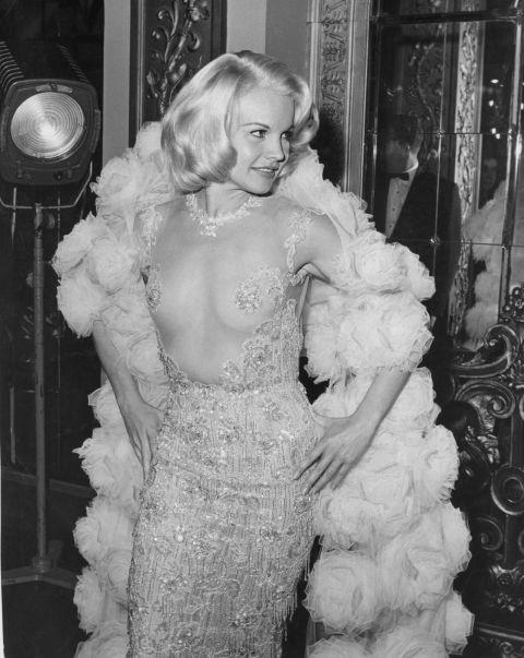 """<p><strong>CARROLL BAKER, 1964</strong><p><p> """"I've tried just acting, but sex sells at the box office,"""" said the actress Carroll Baker, who wore this Pierre Balmain dress to the U.S. and London premieres of her 1964 film The Carpetbaggers. Pictured here in London outside the Plaza Theatre, Baker shows off the provocative transparent top of the dress. The crowd gathered outside the theater reportedly caused a near riot trying to get a peek."""