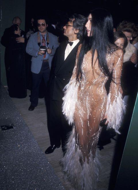 """<p><strong>CHER, 1974</strong><p><p> Cher collaborated on many indelible looks with the designer Bob Mackie, but this is one that really got people talking — and wanting a copy for themselves. She first wore this feathery naked dress to the Metropolitan Museum in 1974, then again on the cover of TIME magazine in 1975. """"When Cher was on the cover of TIME, in her see-through dress, every tired old broad in Hollywood called asking me for one just like it,"""" Mackie said in 2014. Kim Kardashian paid homage to Cher's dress when she attended the Met Gala four decades later."""