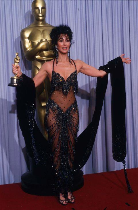 """<p><strong>CHER, 1988</strong><p><p> Cher wore this see-through Bob Mackie gown when she attended the Academy Awards in 1988. Before the show, there was much speculation about what she would wear. """"You don't need to worry about sedate, Cher likes to whoop it up,"""" Mackie teased. The sequined showgirl number became one of the most memorable Oscar dresses in history."""