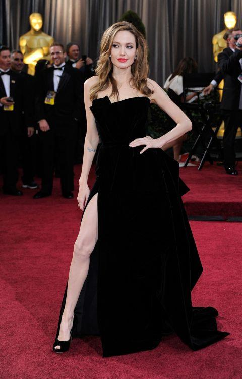 """<p><strong>ANGELINA JOLIE, 2012</strong><p><p> Angelina Jolie is nothing if not committed. It was her insistence on this pose, pushing out her right leg through the high slit of her black Atelier Versace gown, that made the dress — or the image of her wearing it — go viral in 2012. She didn't just thrust on the red carpet, she brought it out when she presented the award for Best Adapted Screenplay. She was then gently mocked by one of the winners, writer Jim Rash. (""""It was a loving tribute,"""" he explained.)"""