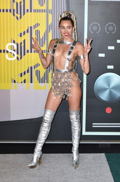 """<p><strong>MILEY CYRUS, 2015</strong><p><p> Before hosting the VMAs in 2015, Miley Cyrus posed for photos in a Versace dress of sorts. Wrote the New York Daily News: """"Miley Cyrus walked the Technicolor-striped carpet before the awards show on Sunday in a custom metallic Versace piece that looked like a crotch chandelier held up with buckled suspenders."""""""