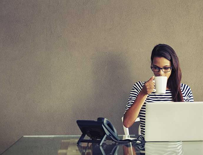 A young woman drinks coffee at her desk.
