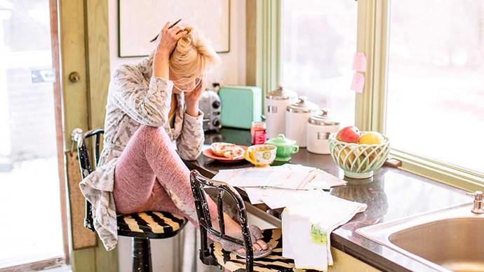 Stressed woman pays bills in kitchen