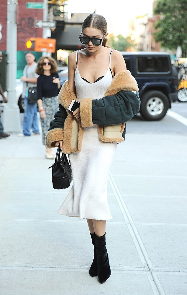 Our girl Gigi has finally boarded the slip dress bandwagon - and we, for one, are thrilled. The model paired her white slip with a pair of black boots, a shearling jacket and a black bra.