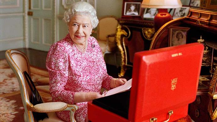 Queen Elizabeth II is seated at her desk in her private audience room at Buckingham Palace with one of her official red boxes.