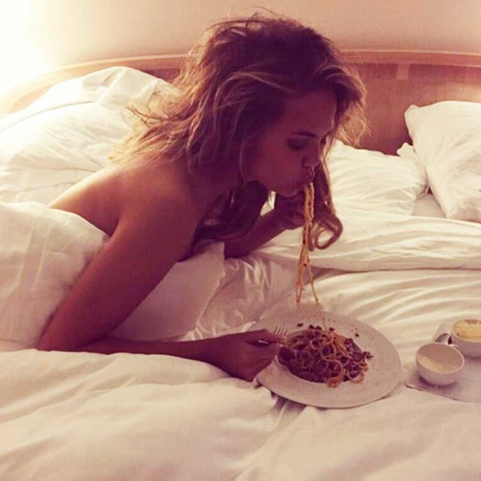 Chrissy Teigen eats pasta in bed