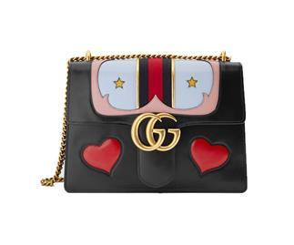 Bold Gucci designer handbag embellished with hearts and stars.