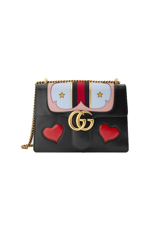 Bold Gucci designer handbag embellished with hearts and stars.