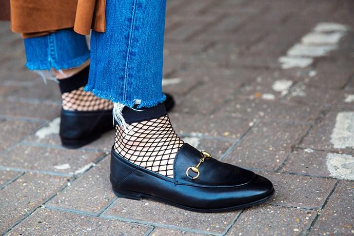 """Frayed denim and fish-net socks add a fun twist to Gucci's classic horsebit loafers."""