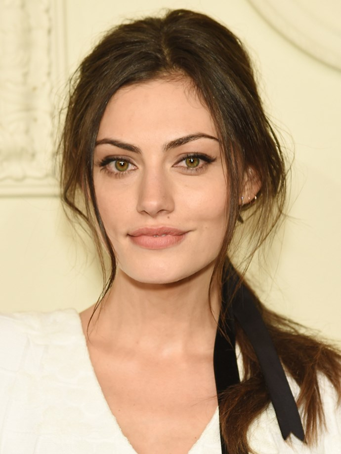 <p>Of course Phoebe Tonkin would wear a cool, loose low ponytail and tie it up with a chic black ribbon.
