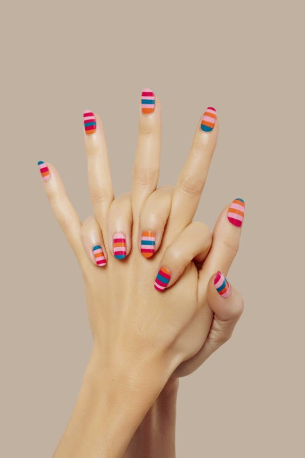 """<strong>Bright Look</strong> <br><br> Rainbow stripes are a no-brainer for summer, and Poole's taking notes from the technicolor runways at Marc Jacobs, Fendi, and Altuzarra. """"When painting your nails with a striped look, start with the most sheer and light colour first,"""" Poole recommends. For those who aren't about perfectly straight lines, Poole also suggested """"choosing 4 or 5 different shades from the '80s revival palette and layering them by using a striping brush to create [...] random order and coloration."""" The irregularity will give you a painterly finish and mask any mistakes, too."""