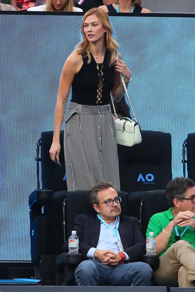 Karlie pairs a striped skirt with a lace-up black top at the tennis.